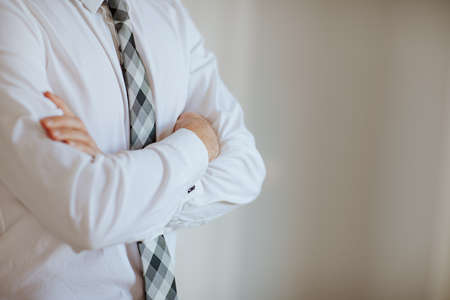 Man in white shirt and gray squared tie posing hands crossed in the white room. Copy space. Focus is at the hands. Business concept.
