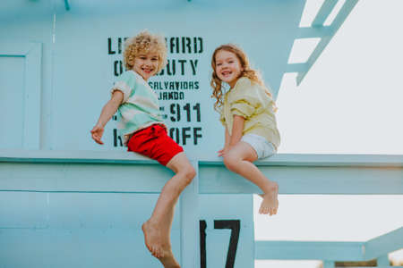 Blond curly young boy and girl in summer clothes sitting up blue lifeguard tower and playing. Summertime.
