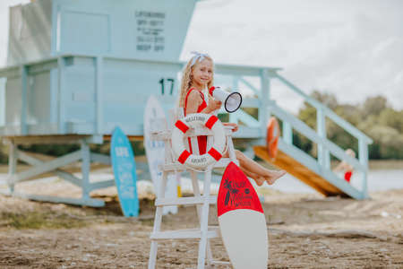 Young pretty curly girl sitting on high white chair with lifeline and posing with megaphone on the beach against blue lifeguard tower.