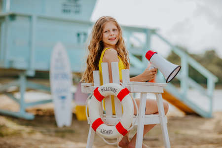 Young pretty curly girl sitting on high white chair with lifeline and posing with megaphone on the beach against blue lifeguard tower. Stock Photo