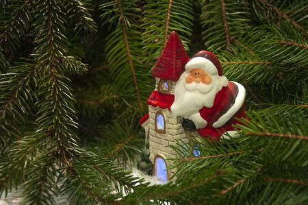 Santa Claus on a house near the branches of a Christmas tree. Background for New Year and Christmas. Stockfoto