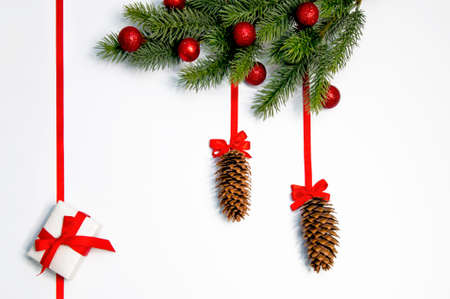 Christmas decorations.Red ribbons and balls, gifts, cones and fir branches on a white background. 免版税图像