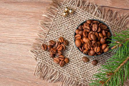 Grains of coffee and a branch of a christmas tree on a wooden table