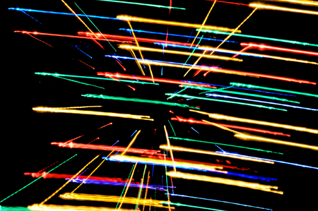 light painting: Abstract multicolored light beams in motion, light painting on a black background