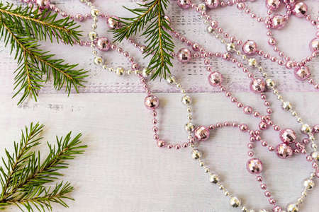 New Year eve sprigs of needles on a wooden background garland and pink and white beads