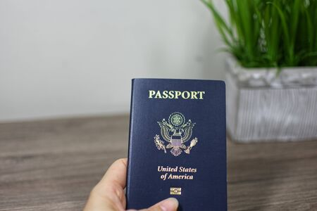Hand holing American passport on wooden table Stok Fotoğraf