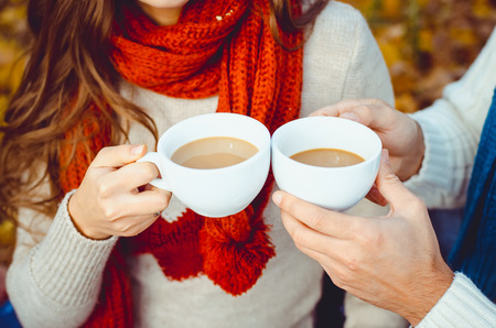Two hands are holding two hot cups of tea photo