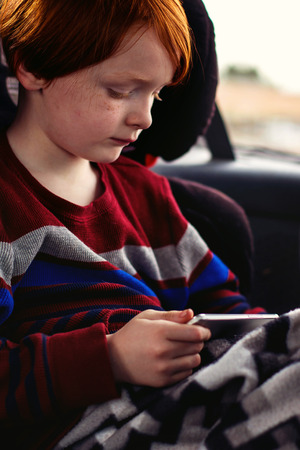 6 year old redheaded boy playing on a phone while in the car photo