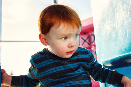 2 year old redheaded boy playing on a playground photo