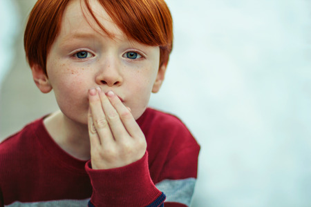 6 year old redheaded boy with his hand to his mouth to blow a kiss photo