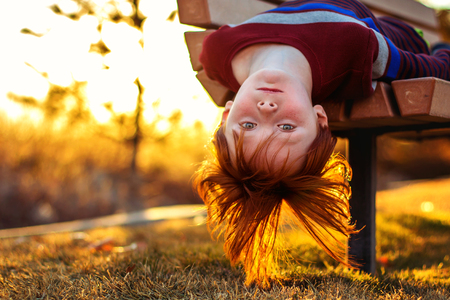 6 year old redheaded boy hanging upside down from a park bench photo