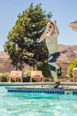 seven year old: seven year old redhead boy jumping into the pool and plugging his nose Stock Photo