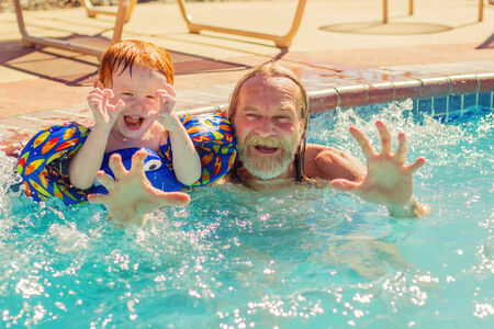 two year old: two year old redhead boy with his grandpa making funny faces in the pool Stock Photo