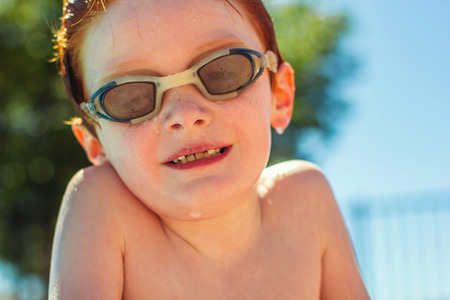 seven year old: seven year old redhead boy wearing goggles at the pool
