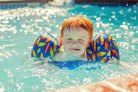 two year old: two year old redhead boy with floaties swimming and making a funny face
