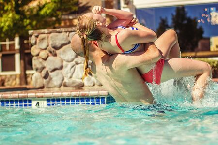 pool preteen: uncle lifting his niece and dunking her in the water
