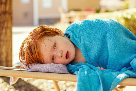 four year old: four year old redhead boy wrapped in a towel laying on a pool chair