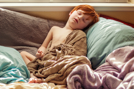 four year old: four year old redhead boy sleeping on the bed