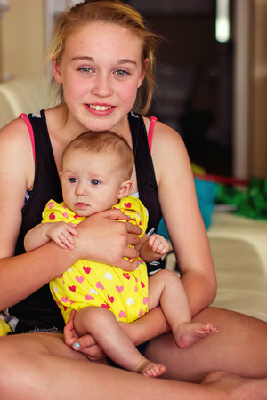 eleven year old tween girl holding her four month old baby sister Stock Photo