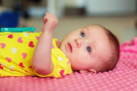 four month old infant girl laying on pink blanket and playing with teething toy