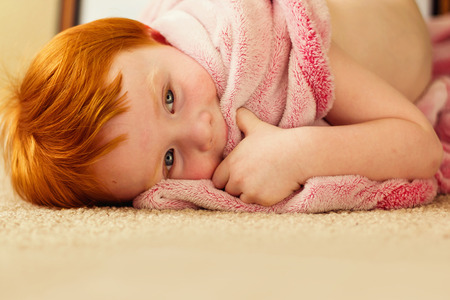 hair wrapped up: two year old redhead boy wrapped in comfortable red blanket laying on the floor