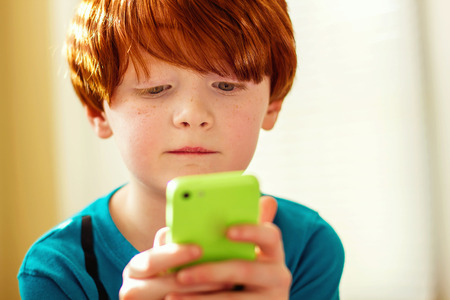 seven year old redhead boy playing with his mother s cell phone Stock Photo