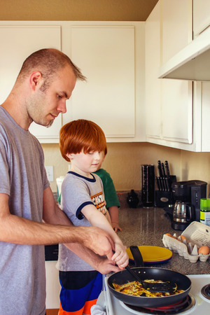 adult man making breakfast in his kitchen with four year old redhead son Stock Photo