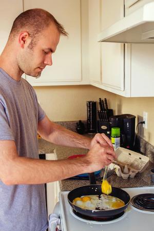 adult man making breakfast in his kitchen