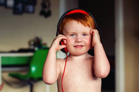 two year old redhead boy playing with headphones
