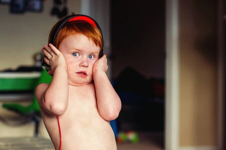 two year old redhead boy playing with headphones and squishing cheeks Stock Photo