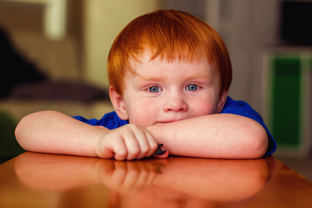 two year old redhead boy sitting with arms resting on table bench