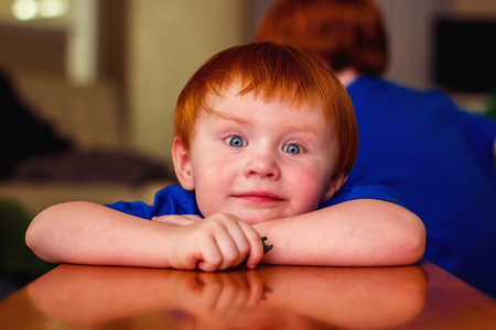 two year old redhead boy sitting with arms resting on table bench with older brother in the background Stock Photo