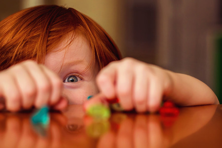 four year old redhead boy playing with toy gems on the table