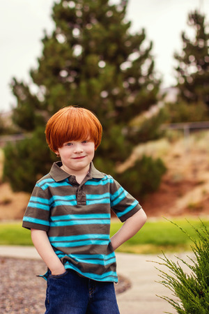 four year old redhead boy standing with his hand in his pocket smiling