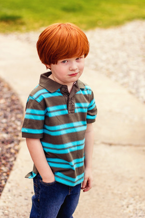 four year old redhead boy standing with his hand in his pocket