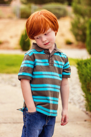 four year old redhead boy standing with his hand in his pocket looking away