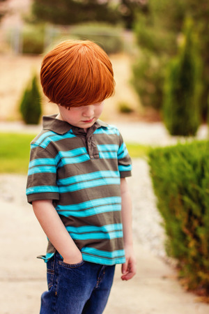 four year odl redhead boy standing with his hand in his pocket looking down