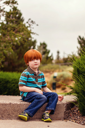 four year old redhead boy sitting on the sidewalk Stock Photo