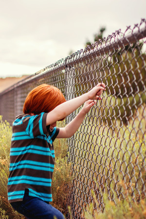 four year old redhead boy playing on the fence Stock Photo