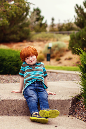 four year old: four year old redhead boy sitting on the sidewalk Stock Photo