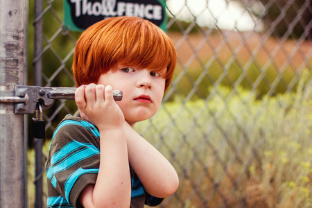 four year old redhead boy holding on to fence gate Stock Photo