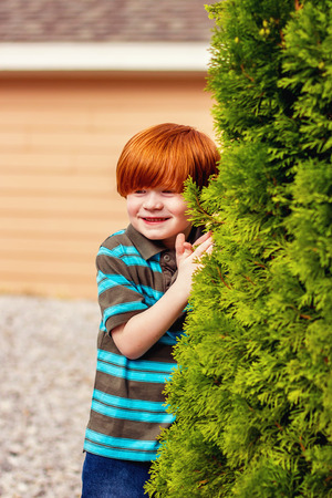 four year old redhead boy standing by a bush