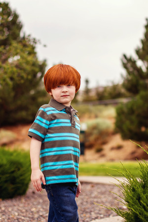four year old redhead boy standing on sidewalk in the summer