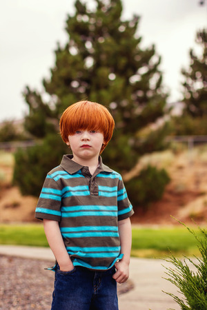 four year old redhead boy standing with his hand in pocket Stock Photo