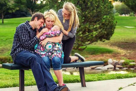 mother holding her infant four month old daughter with husband and tween daughter on a bench