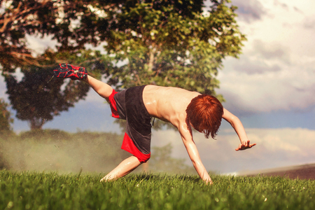 seven year old redhead boy doind a cartwheel in the sprinklers during a hot summer day