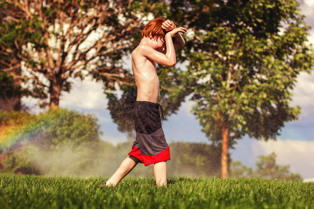seven year old redhead boy playing in the sprinklers during the hot summer