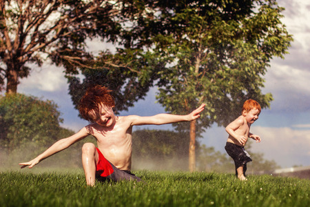 seven and three year old redhead brothers playing in the sprinklers on a hot summer day