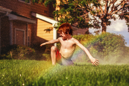 seven year old redhead boy playing in the sprinklers in the summer Stock Photo
