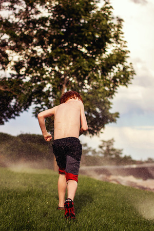 seven year old: seven year old redhead boy running through the sprinklers in the summer